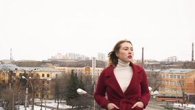 Close-up of young attractive woman in red coat and white turtleneck standing on a roof and looking away. Media. Photo stock photo