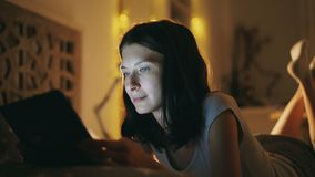 Close-up of young attractive woman using tablet computer at night time lying in bed at home. Close-up of young smiling woman using tablet computer at night time stock footage