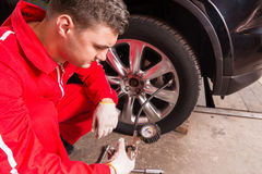 Close up of young auto mechanic checking the air pressure of a t Royalty Free Stock Images