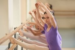 Close up young ballerina with her legs on barre. Beautiful ballet girl training ballet move in ballet hall. Lesson of ballet dance Royalty Free Stock Image