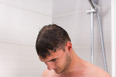 Close up young bare man looking down while taking shower. In the modern tiled bathroom Royalty Free Stock Images