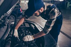 Close up of young bearded expert specialist appraising the damage for repairing car at work shop, mounting it, arms in white knit. Ted gloves, hat and special royalty free stock images