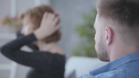 Close up young bearded man looking at blurred figure of a senior mature woman touching her hair sitting near the man on. Close up young bearded man looking at stock video