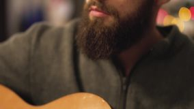 Close-up of young bearded man in Santa`s hat playing guitar sitting in front of Christmas tree. New Year and Christmas. Close-up of a young bearded man in Santa` stock footage