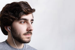 A close-up of young bearded stylish man relaxing indoors alone, listening to music tracks on earphones  dreaming about something. Royalty Free Stock Images