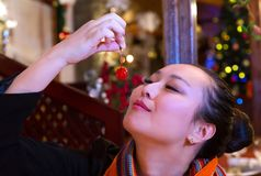 Woman savouring a cherry. Close-up of a young beautiful Asian woman holding a cherry and smelling it. Woman savours the moment before eating a cherry. Warm Royalty Free Stock Image