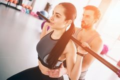 Close up of young and beautiful boy and girl exercising in gym. She is doing some squads using bodybar while her trainer. Is supporting her. Cut view stock image