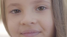 Close-up of a young beautiful brown-eyed girl with brunette hair smiling to the camera. Innocent caucasian child. Standing in the autumn park stock video
