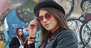 Close up of the young beautiful charming girl in hipster style, sunglasses and black hat looking at the camera and