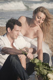 Close up of young beautiful couple sitting at the beach Royalty Free Stock Photo