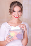 Close up of a young beautiful smiling woman taking a napking from a colorful purse, in a blurred background Royalty Free Stock Photography