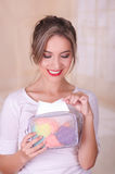 Close up of a young beautiful smiling woman taking a napking from a colorful purse, in a blurred background Royalty Free Stock Images