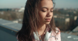 Close up of young beautiful woman enjoying time on a rooftop. Fashion young African American woman relaxing in a city with headphones Stock Images