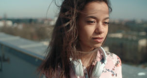 Close up of young beautiful woman enjoying time on a rooftop. Fashion young African American woman relaxing in a city with headphones Stock Image