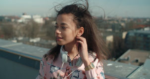 Close up of young beautiful woman enjoying time on a rooftop. Fashion young African American woman relaxing in a city with headphones Royalty Free Stock Image