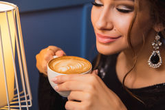 Close up of young beautiful woman hands holding hot cup of cappuccino Stock Image