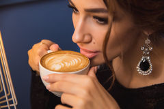 Close up of young beautiful woman hands holding hot cup of cappuccino Royalty Free Stock Image