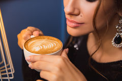 Close up of young beautiful woman hands holding hot cup of cappuccino Royalty Free Stock Photo