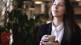 Close up of young beautiful woman hands holding and smell hot cup of coffee or tea with milk. stock footage