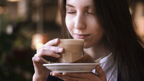 Close up of young beautiful woman hands holding and smell hot cup of coffee or tea with milk. stock video footage