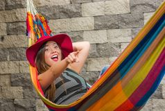 Close up of young beautiful woman wearing a red fashion hat and relaxing in a hammock, pointing somewhere with her arm. In blurred background Royalty Free Stock Photo