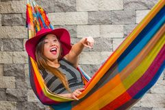 Close up of young beautiful woman wearing a red fashion hat and relaxing in a hammock, pointing somewhere with her arm. In blurred background Stock Photography