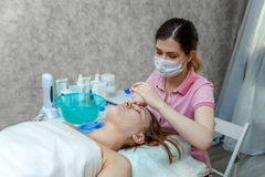 Woman getting face treatment with white nourishing creme in spa salon royalty free stock photography
