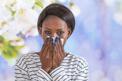 Close up of young black business woman blowing her nose Royalty Free Stock Images