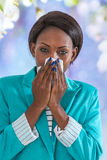 Close up of young black business woman blowing her nose Stock Images