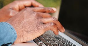 Close up of young black man hands. He is wearing a shirt and typing at his laptop keyboard. Concept of a freelance job. Locked down real time close up shot stock footage