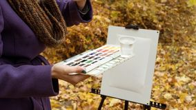 Close-up of young girl artist that paints a picture on the easel in the autumn park. Close-up of young blonde girl artist in purple coat that paints a picture on royalty free stock photo