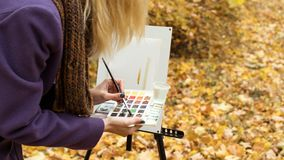 Close-up of young girl artist that paints a picture on the easel in the autumn park. Close-up of young blonde girl artist in purple coat that paints a picture on stock photography