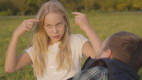 Close-up of a young blonde girl talking emotionally to her father. Family spending autumn day together sitting on the
