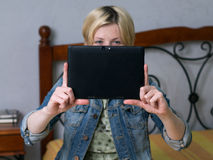 Close up young blonde woman holding a tablet and smiling royalty free stock photo