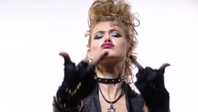 Close up of a young blonde woman with silver makeup and rocker clothes, showing middle finger. Blonde rocker woman in black leather clothes with metal spikes stock footage