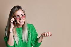 Close up Young blonde Woman Talking to Someone on her Mobile Phone While Looking Into the Distance with Happy Facial Expression royalty free stock photo