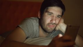 Close-up of young bored man having internet addiction and insomnia using smartphone lying in bed at home at night. Time Royalty Free Stock Photography