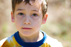 Close up of a young boy. Young boy staring into the camera with beautiful brown eyes Stock Images
