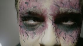 Close up of a young boy wearing halloween zombie face paint makeup and costume looking straight to camera -. Close up of a young boy wearing halloween zombie stock footage