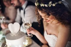 A close-up of a young bride sitting at a table on a wedding, holding a glass of wine. A close-up of a young bride sitting at a table on a wedding, holding a stock images