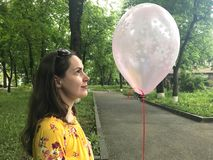 Close up of a young brunette woman with pink balloon in her hands. Side view royalty free stock image