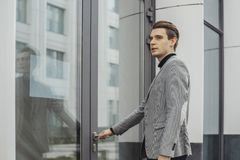 Close up of young business man opening door of modern business center. royalty free stock images