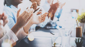 Close up of young business partners applauding to reporter after listening report at seminar. Professional education. Work meeting, presentation or coaching Royalty Free Stock Images