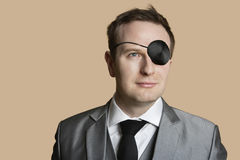 Close-up of a young businessman with eye patch looking away over colored background Stock Images