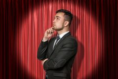Close-up of young businessman standing in half-turn looking away and up, with hand on chin, lit up by spotlight, against royalty free stock images