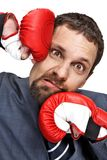 Close-up young businessman struck in the face by hands in boxing gloves. On grey background Royalty Free Stock Images