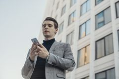 Close up of young businessman talking by mobile phone next to business center. stock images