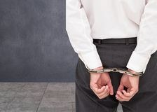 Close up on young businessman wearing handcuffs Royalty Free Stock Photography