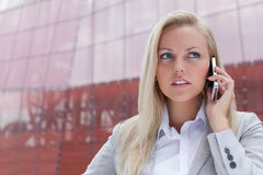 Close-up of young businesswoman communicating on mobile phone against office building Royalty Free Stock Photo