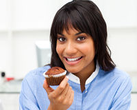 Close-up of a young businesswoman eating a muffin Royalty Free Stock Images
